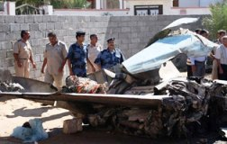 Libyan security officials inspect the wreckage of the aircraft.