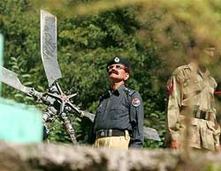 A Pakistan army soldier, right, and a police officer guard the wreckage of crashed helicopter in Mujhoi