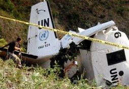 A peacekeeper walks towards a crashed UN plane in Pays Pouri, Haiti, Saturday, Oct. 10, 2009. U.N. helicopters reached the remote site of a plane crash that killed 11 peacekeepers when a surveillance flight slammed into a mountain in Haiti on Friday. (AP Photo/Diev-nalio- Chery)