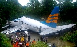 Rescuers gather near the wreckage of a Boeing 737 operated by Merpati Nusantara Airlines after it skidded off the runway at Rendani airport in Manokwari, Papua province, Indonesia, on Tuesday. (AP Photo/Abdul Muin)