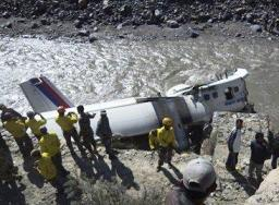 Nepalese rescuers and other people stand near the wreckage of a Nepal Airlines plane that crashed on the banks of Kaligandaki river at Jomsom, some 200 kilometers (125 miles) northwest of Katmandu, Nepal, Thursday, May 16, 2013. (AP Photo/Ananda Subedi)