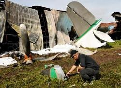 Civil aviation officials investigate at a warehouse after a private plane crashed in the Las Pinas suburb of Manila on October 17, 2009. Four people were killed as a private plane crashed on October 17 into a warehouse in a suburb of the Philippine capital, witnesses and radio reports said. (Getty Images)