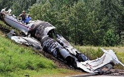 Investigators look over the debris left by the Learjet that was carrying former Blink 182, drummer, Travis Barker, and Adam Goldstein, also know as DJ-AM, on the outskirts of the Columbia Metropolitan Airport, Saturday, Sept. 20, 2008, in Columbia, S.C. Barker and Goldstein were critically injured, and two other passengers and two crew members were killed. (AP Photo/Brett Flashnick)