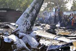 People gather around the scene where a L-39C plane crashed at a slum 300 meters away from the international airport Antonio Jose de Sucre in Cumana, capital of Venezuelan state of Sucre, March 21, 2010. The light plane crashed into three houses on Sunday killed at least 6 people and hurt 3. (Xinhua/Jose Guilarte)