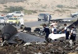 A rescue team carry the body of a Sudanese cargo plane crew member after the plane crashed shortly after take-off from Sharjah International Airport north of Dubai, in Sharjah, United Arab Emirates Wednesday Oct. 21, 2009. A Sudanese cargo plane crashed Wednesday shortly after takeoff from Sharjah International Airport north of Dubai, killing the entire six-member crew. The Boeing 707 went down in an unpopulated area about two miles (three kilometers) from the airport. (AP Photo/Kamran Jebreili)