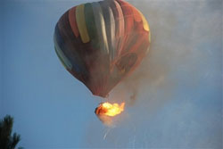 A hot air balloon's basket bursts into flames shortly after takeoff.