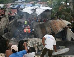 Residents look on as rescuers carry bodies from the wreckage of a twin-prop Nomad aircraft of the Philippine Air Force that crashed into a residential area in Cotabato city, southern Philippines Thursday, Jan. 28, 2010. The crash killed a senior air force commander and seven other people aboard, officials said. (AP Photo/Edward Dequina)