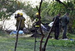 Firefighters and police officers inspect the site where a Colombian air force helicopter crashed in a rural area of the town of Sabanagrande, Colombia, Monday, April 30, 2012. Two officials who spoke on condition they not be further identified put the death toll at 13. Both say they were not authorized to disclose the number. (AP Photo)