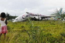 Caribbean Airlines jet is seen broken at Cheddi Jagan International airport outside Georgetown July 30, 2011. Yjr packed Caribbean Airlines jet carrying 163 people crashed and broke in two Saturday as it landed in Guyana at night, injuring several passengers but killing no one. The Boeing 737-800 overshot the runway and burst through a perimeter fence after arriving at Georgetown's Cheddi Jagan airport just past midnight from New York. The front of the plane snapped off and it stopped meters from a deep jungle ravine. REUTERS/Neil Marks